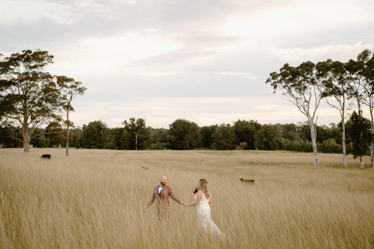 A newly wedded couple walking in a beautiful field at their south coast backyard wedding.